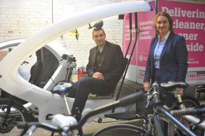 IoC CEO Tracey Worth with Sam Clarke aboard a cargo cycle in the arches.